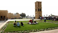 Indian, Pakistani labourer rest on lawn, greet square at Al Ghubaiba Metro Stock Footage