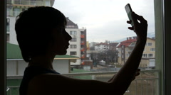 By a window silhouette take selfie picture via smartphone Stock Footage