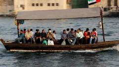 Abra boat sail on water, bench full of passengers, tracking shot from shore Stock Footage