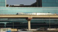 Dubai metro train move at railroad flyover against glass building facade, reflex Stock Footage
