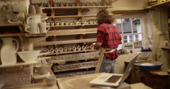 4K Small business owner in pottery studio looking at computer & checking sales Stock Footage