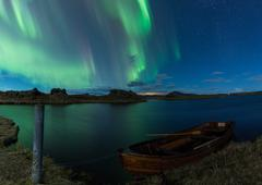 Aurora borealis in Iceland above a lake with boat - stock photo