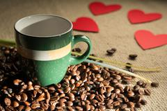Cup of coffee with beans and hearts scattered paper - stock photo