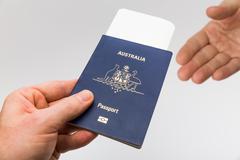 Handing over passport at border control - stock photo