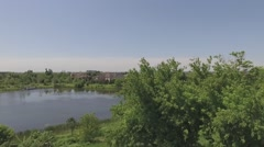 Aerial fly over pond and community overlooking theme park Stock Footage