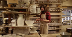 4K Business owner in pottery workshop looking at tablet computer &checking stock Stock Footage