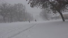 People with difficulty walking on snow-covered street in bad stormy weather Stock Footage
