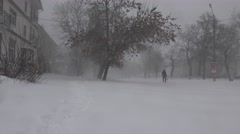 People with difficulty walking on snow-covered street in bad stormy weather - stock footage