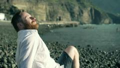 Happy man sitting on the shingle beach and relaxing, steadycam shot Stock Footage