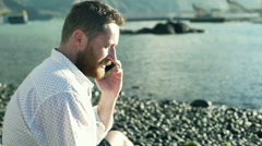Happy man chatting on cellphone and sitting on the shingle beach Stock Footage