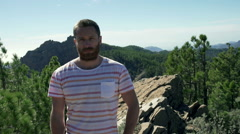Man standing in the mountains and doing serious look to the camera Stock Footage