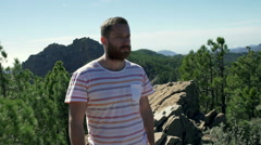 Man standing in the mountains and smiling to the camera Stock Footage