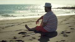 Man sitting on the sandy beach and listening music, steadycam shot Stock Footage