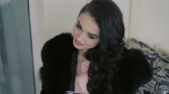 Portrait of elegant girl in fur sitting in cafe and looking on the phone. 4K Stock Footage