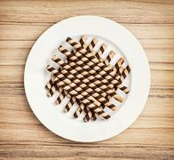 Chocolate rolls on the white plate, confectionery theme - stock photo