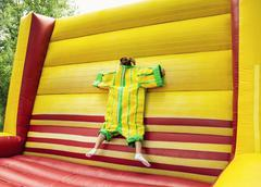 Young woman in plastic dress in a bouncy castle imitates a fly on velcro wall - stock photo
