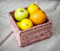 Wicker basket with apples, oranges and lemons, healthy food theme - stock photo