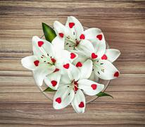 Arrangement of white lilies with more little red hearts in the glass bowl. Va Stock Photos