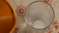 Pouring milk into a glass from a jug Stock Footage