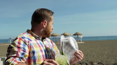 Man fluttering himself because of heat and drinking beverage, steadycam shot Stock Footage