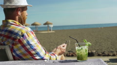 Man relaxing on the beach and listening music on earphones, steadycam shot Stock Footage