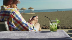 Man playing game on smartphone and sitting on the beach, steadycam shot Stock Footage