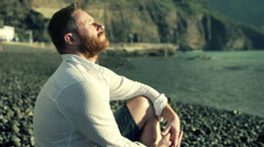 Handsome man sitting on the shingle beach and relaxing on the sun Stock Footage