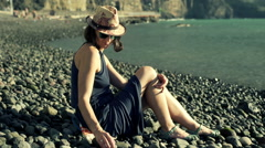 Thoughtful woman sitting on the shingle beach and touching rocks, steadycam shot Stock Footage