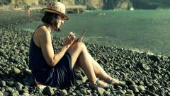 Woman sitting on the shingle beach and browsing internet on smartphone, steadyca Stock Footage
