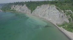Aerial shot cliff by the water camera pulling closer in a sunny day Arkistovideo