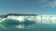 Moving shot sailing amongst small icebergs and glacier wall Stock Footage