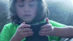 Little boy playing game on smartphone and looking occupied, steadycam shot Stock Footage