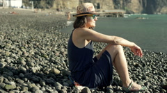 Beautiful woman sitting on the shingle beach and relaxing, steadycam shot Stock Footage