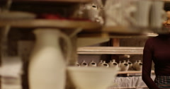 """Attractive woman holding """"open sign"""" in a pottery studio. Slow motion. Stock Footage"""
