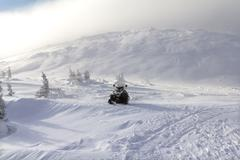 Snowmobile in the mountains - stock photo