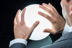 Cropped image of businessman predicting future on crystal ball against black  Stock Photos