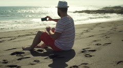 Man sitting on the sandy beach and doing selfie on smartphone, steadycam shot Stock Footage