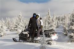 Man and woman on a snowmobile. Stock Photos