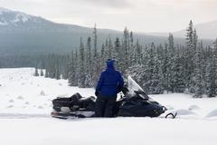 Woman on snowmobile in the mountains. Stock Photos