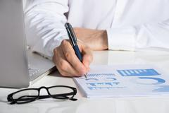 Midsection of businessman analyzing financial charts at office desk Stock Photos