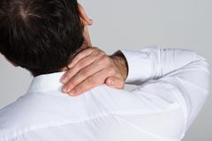 Rear view of businessman suffering from neck ache against white background Kuvituskuvat