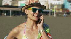 Woman standing on the sandy beach and chattin on cellphone, steadycam shot Stock Footage