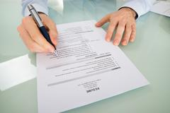 Close-up Of A Businessperson With Resume At Desk Stock Photos