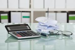 Receipts In Paper Nail With Calculator And Eyeglasses On Desk Stock Photos