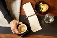 Hand holding a morning coffee with notepad and pastry nearby Stock Photos