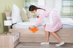Young Female Housekeeper Cleaning Bed In Hotel Room - stock photo