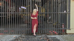 Blond Woman In Red Dress Leaning Against Metal Gate Stock Footage