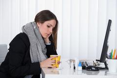 Young Businesswoman With Cup Of Hot Beverage Sitting At Desk - stock photo