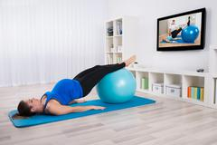 Young Pregnant Female Exercising In Front Of Television - stock photo