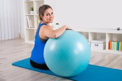 Happy Woman With Fitness Ball Sitting On Exercise Mat - stock photo